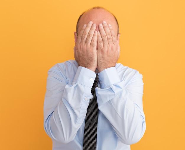 Mężczyzna w średnim wieku ubrany w białą koszulkę z krawatem zakrył twarz rękami odizolowanymi na pomarańczowej ścianie