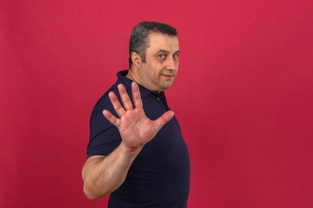 Mężczyzna w średnim wieku ubrany w koszulkę polo z uśmiechem na twarzy i pokazując numer pięć z palcami na izolowanych różowej ścianie