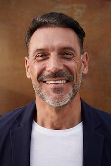 Mężczyzna w średnim wieku ubrany w kurtkę, śmiejąc się szczęśliwy