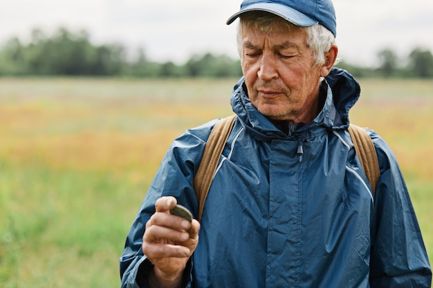 Mężczyzna w średnim wieku, ubrany w niebieską kurtkę, trzymający starą monetę znalezioną na łące,