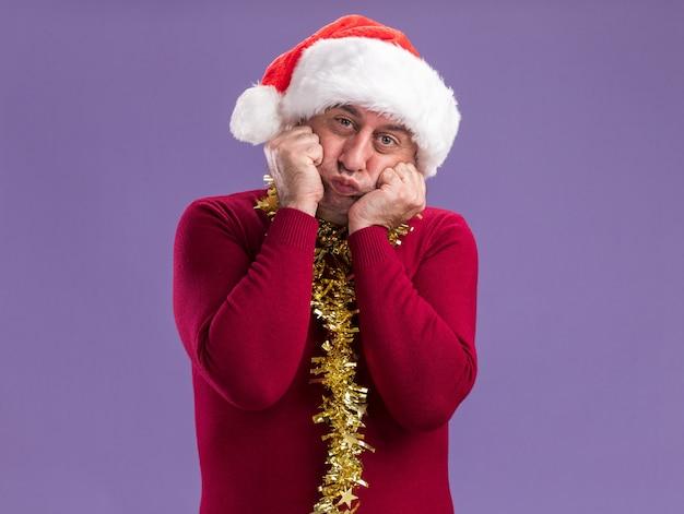 Mężczyzna w średnim wieku ubrany w świąteczny santa hat z blichtrem na szyi patrząc na kamery z mylącym wyrazem dmuchania policzków stojącego na fioletowym tle