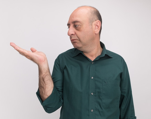 Mężczyzna w średnim wieku ubrany w zielony t-shirt udając, że trzyma coś w ręku na białym tle na białej ścianie z miejsca na kopię