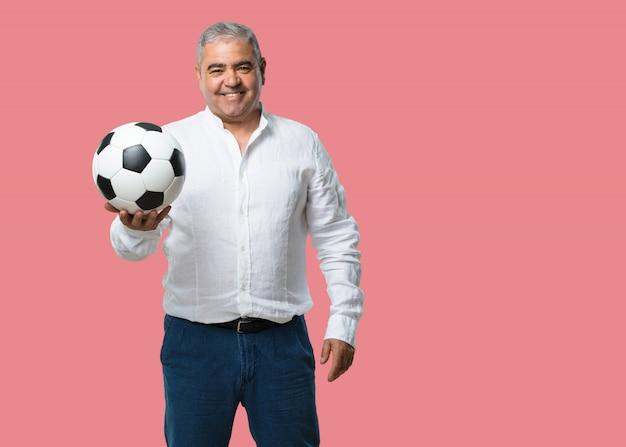 Mężczyzna w średnim wieku uśmiechnięty i szczęśliwy, trzymając piłkę nożną, postawa konkurencyjna, podekscytowany, aby zagrać w grę