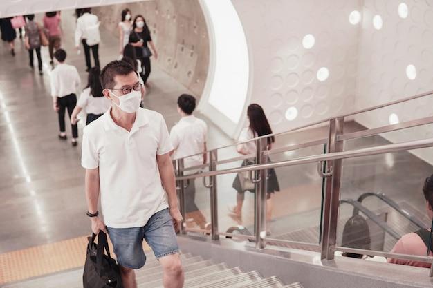 Mężczyzna w średnim wieku w azji w okularach i maski medyczne chodzenie z tłumem w centrum handlowym, wybuch koronawirusa wuhan, zanieczyszczenie powietrza i koncepcja zdrowia