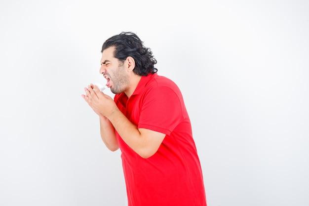 Mężczyzna w średnim wieku w czerwonej koszulce cierpi na kaszel i wygląda niezdrowo, widok z przodu.