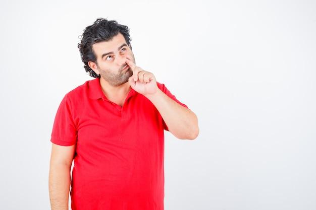 Mężczyzna w średnim wieku w czerwonej koszulce szturcha nos i wygląda zamyślony, widok z przodu.