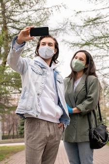 Mężczyzna w średnim wieku w dorywczo strój stojący w parku i fotografujący z żoną w masce