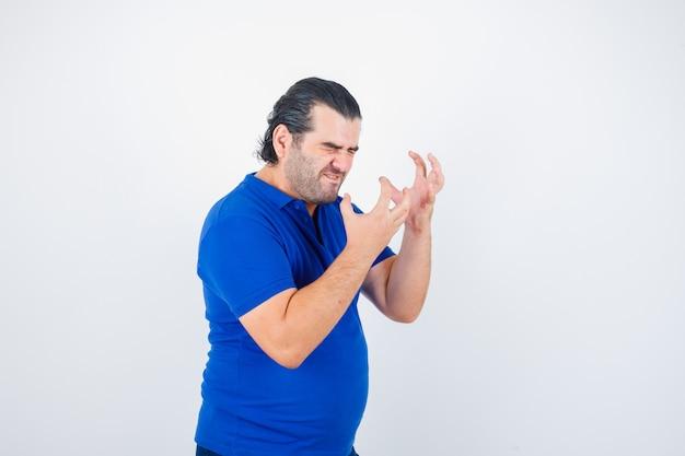 Mężczyzna w średnim wieku w koszulce polo, trzymając ręce w sposób agresywny i patrząc wściekły, widok z przodu.