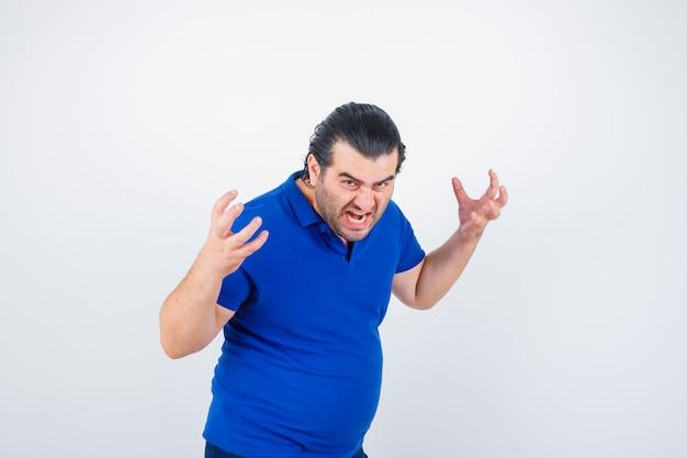 Mężczyzna w średnim wieku w koszulce polo, trzymając ręce w sposób agresywny i patrząc zły, widok z przodu.
