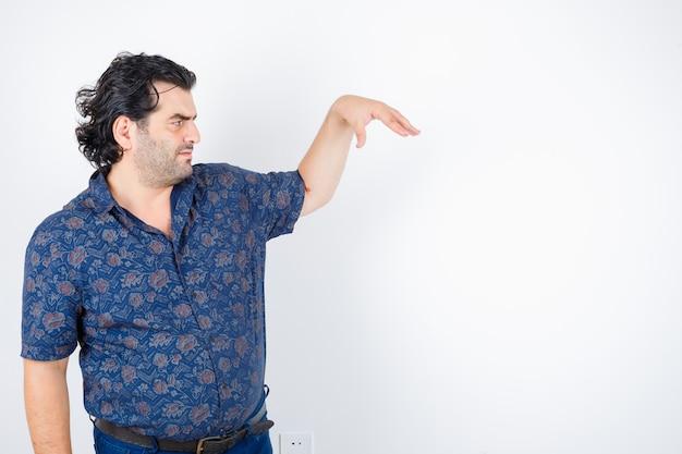 Mężczyzna w średnim wieku w koszuli udaje, że trzyma coś i wygląda poważnie, widok z przodu.