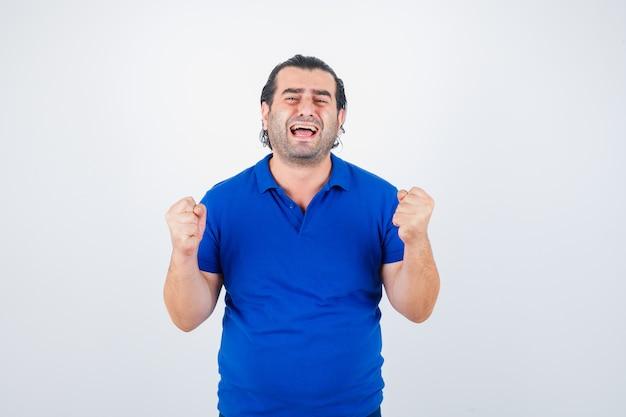 Mężczyzna w średnim wieku w niebieskiej koszulce pokazuje gest zwycięzcy i szuka szczęścia, widok z przodu.