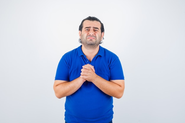 Mężczyzna w średnim wieku w niebieskiej koszulce pokazuje splecione dłonie w błagalnym geście i wygląda z nadzieją, widok z przodu.