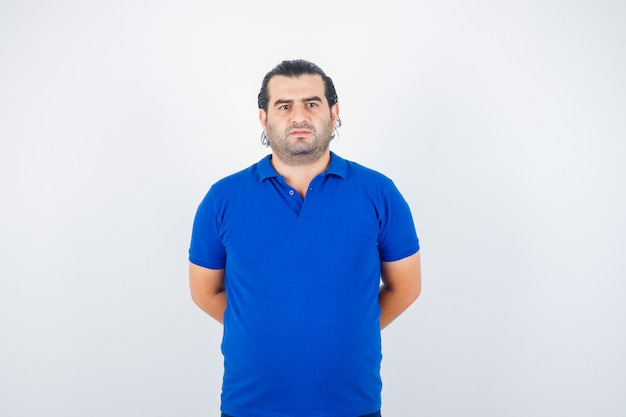 Mężczyzna w średnim wieku w niebieskiej koszulce, trzymając się za ręce za plecami i patrząc pewnie, z przodu.