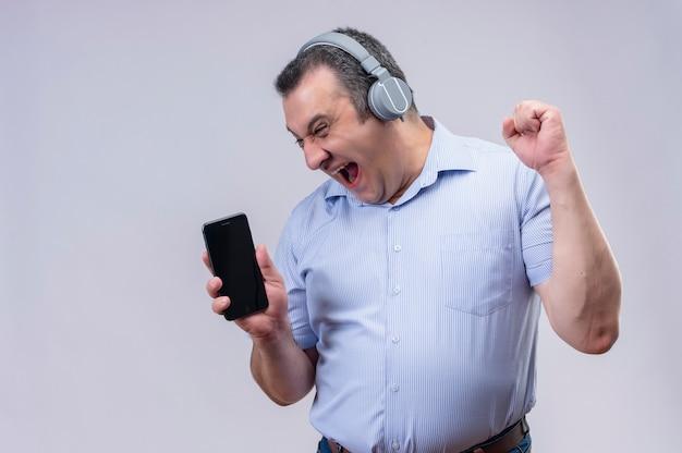 Mężczyzna w średnim wieku w niebieskiej koszuli w paski z wrzeszczącą twarzą w słuchawkach pokazujący smartfon na białym tle