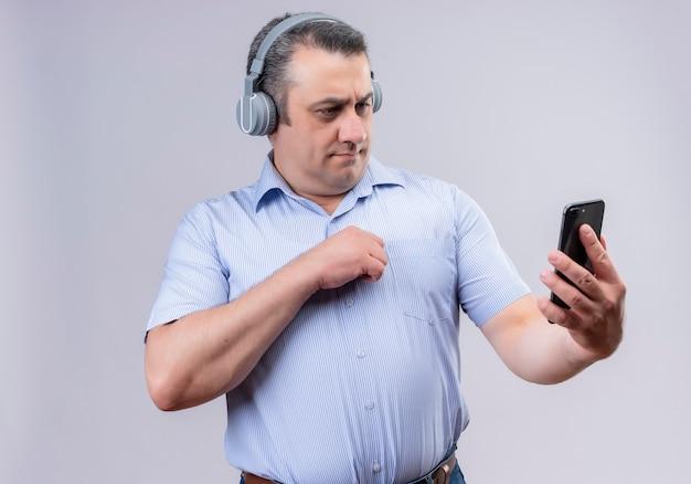 Mężczyzna w średnim wieku w niebieskiej koszuli w pionowe paski na sobie słuchawki, patrząc na swój telefon komórkowy, stojąc na białym tle