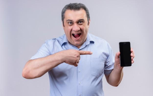 Mężczyzna w średnim wieku w niebieskiej koszuli w pionowe paski, trzymając usta otwarte i wskazując palcem wskazującym swój telefon komórkowy, stojąc na białym tle