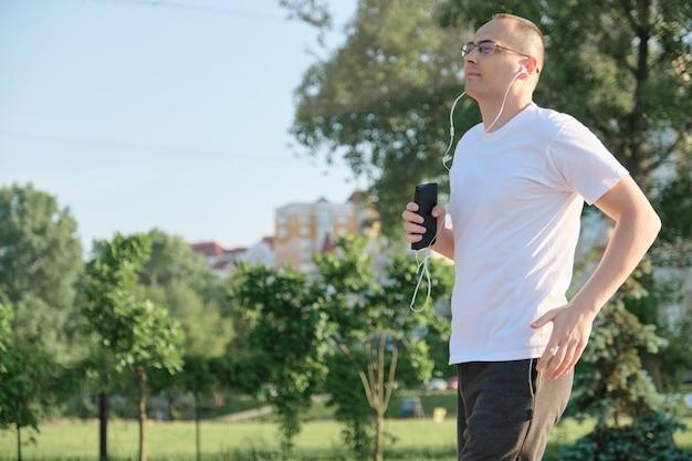 Mężczyzna w średnim wieku w okularach biegnie przez park miejski ze słuchawkami