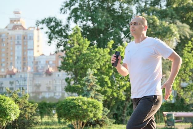 Mężczyzna w średnim wieku w okularach biegnie przez park miejski ze słuchawkami.