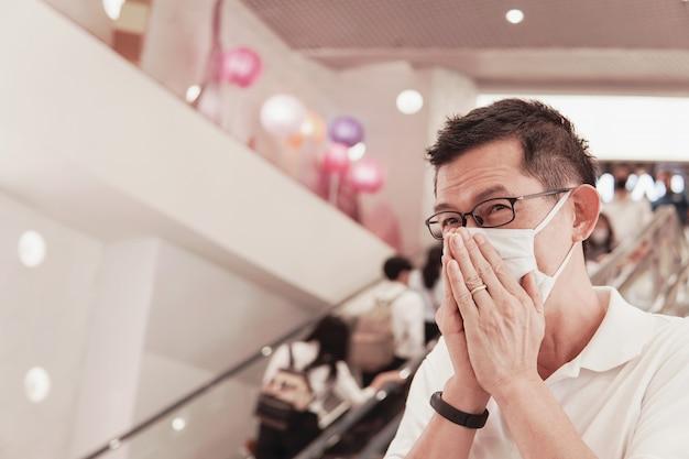 Mężczyzna w średnim wieku w okularach i medycznej masce na twarz, kichanie i kaszel, wybuch koronawirusa wuhan, zanieczyszczenie powietrza i koncepcja zdrowia