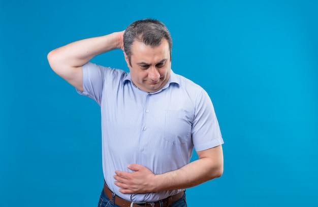 Mężczyzna w średnim wieku w rozmytej koszuli w paski myśli, czując głód i trzymając rękę na głowie na niebieskim tle
