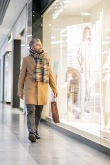 Mężczyzna w średnim wieku w stylowym stroju codziennym, patrząc na jedną z dużych witryn sklepowych, przechodząc obok z papierową torbą po zakupach