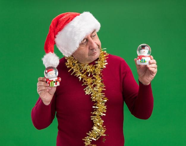 Mężczyzna w średnim wieku w świątecznej czapce mikołaja z blichtrem na szyi trzymający świąteczne kule śnieżne wyglądający na zdezorientowanego i mającego wątpliwości stojąc na zielonym tle