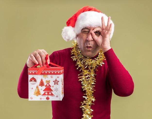 Mężczyzna w średnim wieku w świątecznej czapce mikołaja ze świecidełkiem na szyi trzyma prezent świąteczny patrząc na kamerę przez palce, robi ok, śpiewa stojąc na zielonym tle