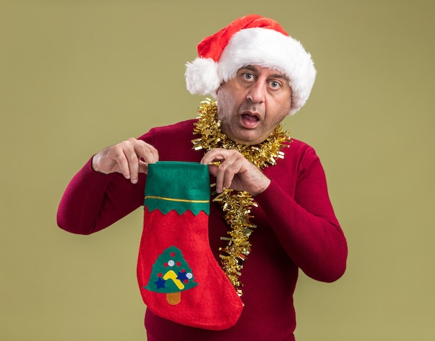 Mężczyzna w średnim wieku w świątecznej czapce mikołaja ze świecidełkiem na szyi trzyma świąteczną skarpetę patrząc na kamerę zaskoczony i zdumiony stojąc na zielonym tle