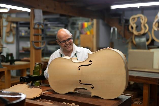 Mężczyzna w średnim wieku w swoim warsztacie instrumentów