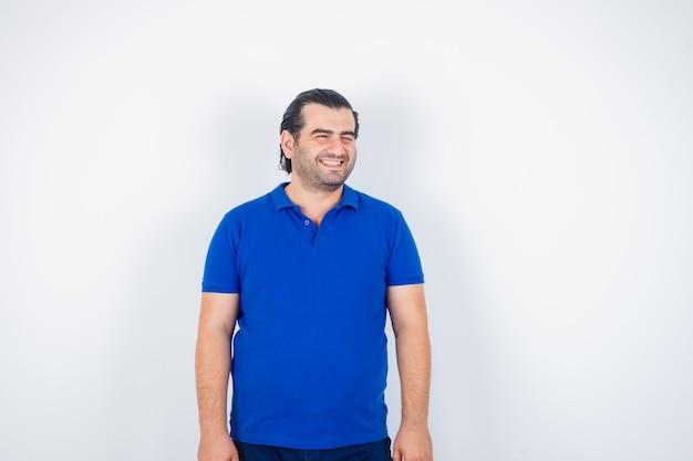 Mężczyzna w średnim wieku w t-shirt, odwracając wzrok i patrząc szczęśliwy, widok z przodu.