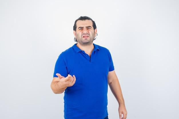 Mężczyzna w średnim wieku, wskazując na aparat w niebieskiej koszulce i patrząc zdziwiony, widok z przodu.