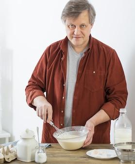 Mężczyzna w średnim wieku wyrabiania ciasta naleśnikowego na białej kuchni