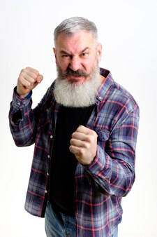Mężczyzna w średnim wieku z gestem obrony pięści, zły i zdenerwowany mężczyzna na białym tle, gotowy do walki, boi się problemów