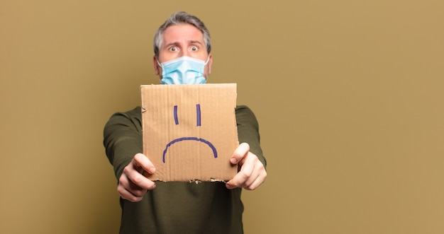 Mężczyzna w średnim wieku z maską ochronną i smutną koncepcją