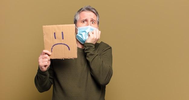 Mężczyzna w średnim wieku z maską ochronną i smutną twarzą na tekturze
