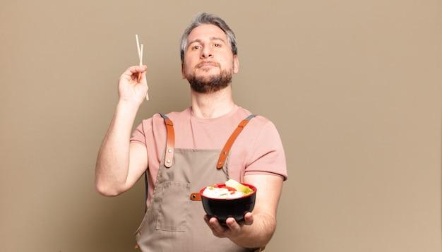 Mężczyzna w średnim wieku z miską na ramen
