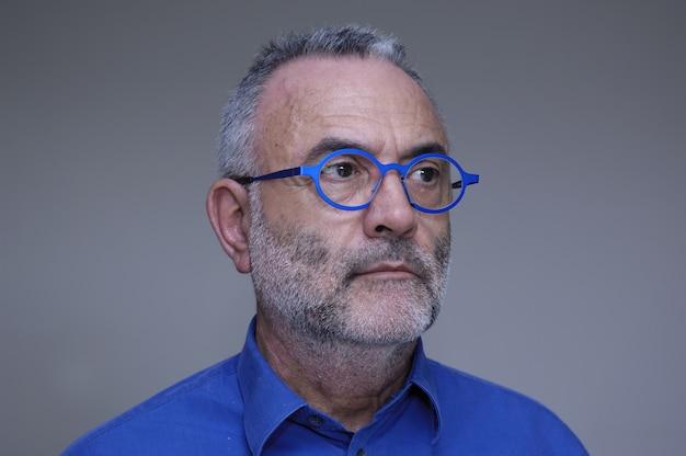 Mężczyzna w średnim wieku z niebieską koszulą i okularami