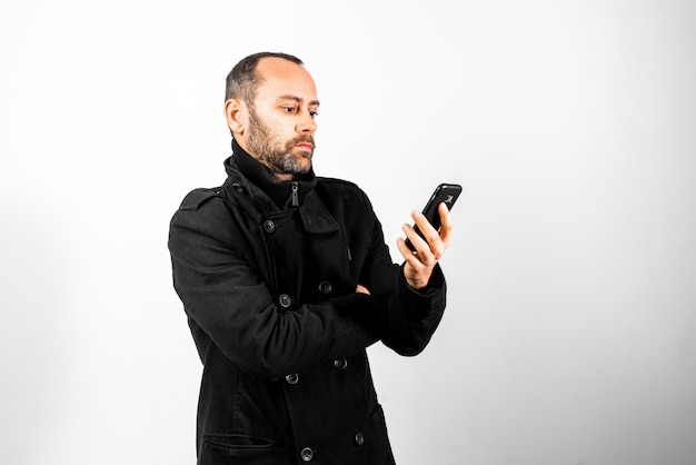Mężczyzna w średnim wieku z płaszczem słucha uważnie rozmowy w swoim telefonie komórkowym