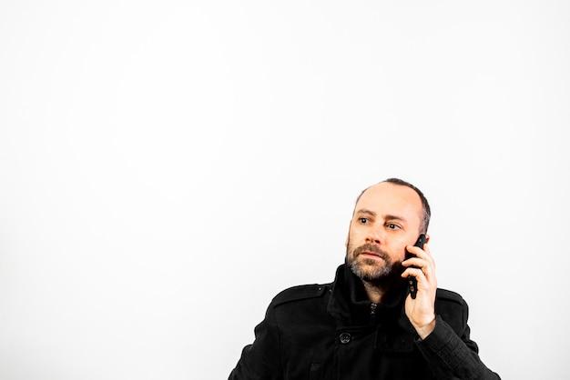 Mężczyzna w średnim wieku z płaszczem słucha uważnie rozmowy w telefonie komórkowym