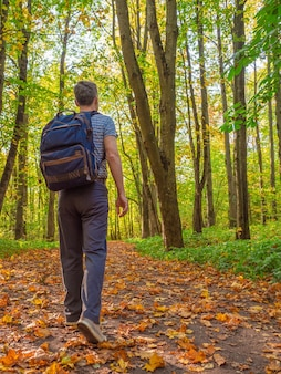 Mężczyzna w średnim wieku z plecakiem spaceruje po jesiennym lesie.