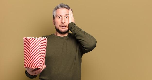Mężczyzna w średnim wieku z wiaderkiem popcornu