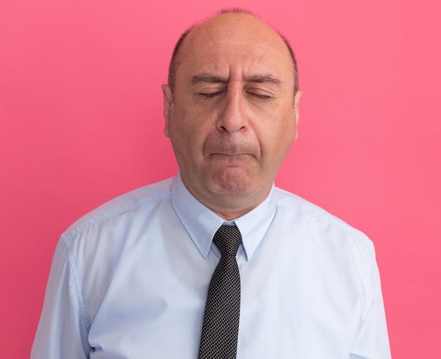 Mężczyzna w średnim wieku z zamkniętymi oczami na sobie białą koszulkę z krawatem na białym tle na różowej ścianie