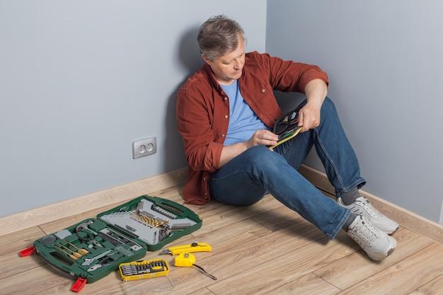 Mężczyzna w średnim wieku z zestawem narzędzi do naprawy na drewnianej podłodze