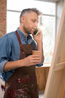 Mężczyzna w średnim wieku ze szklanką kawy stojąc przed sztalugą w studio, rozmawiając z kimś na telefonie komórkowym
