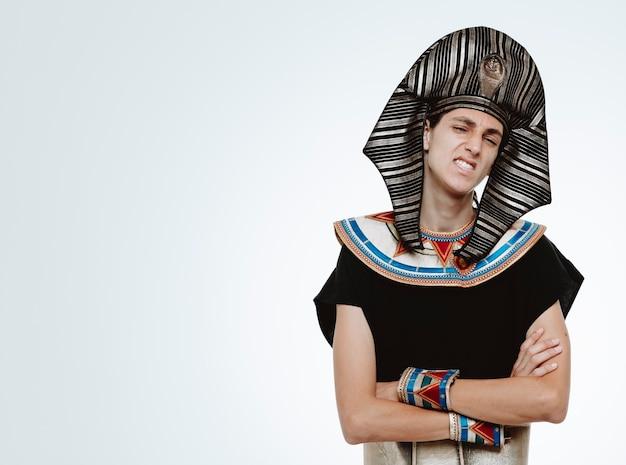 Mężczyzna w starożytnym egipskim stroju jest niezadowolony, robiąc krzywe usta z rękami skrzyżowanymi na biało