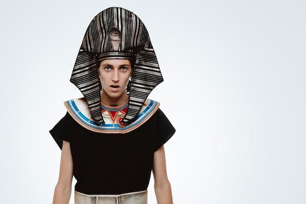 Mężczyzna w starożytnym egipskim stroju jest zdumiony i zaskoczony na białym tle