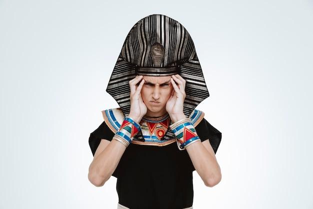 Mężczyzna w starożytnym egipskim stroju jest zły i zirytowany dotykając swoich skroni na białym tle