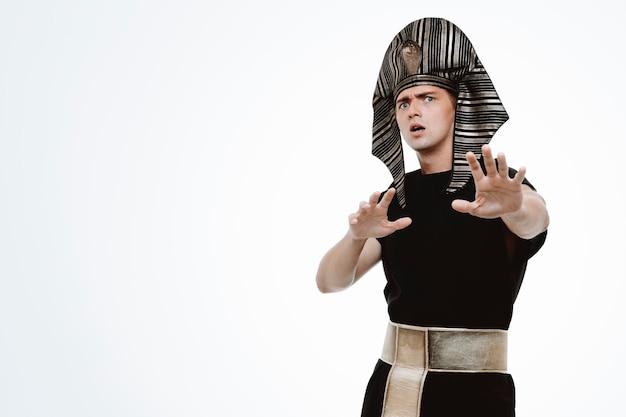 Mężczyzna w starożytnym egipskim stroju martwi się wykonywaniem gestu zatrzymania rękami na białym