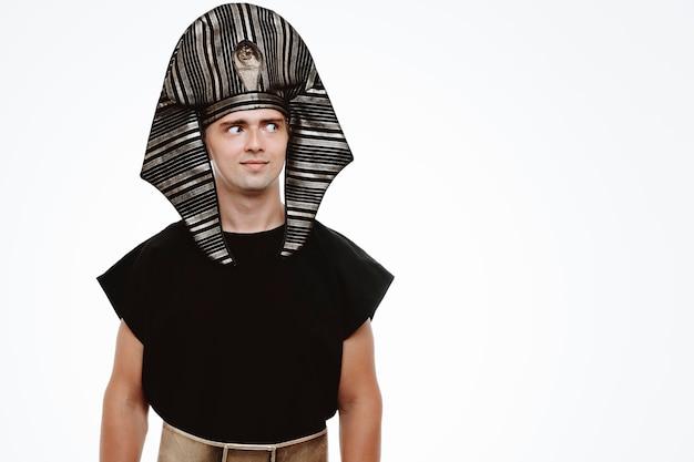 Mężczyzna w starożytnym egipskim stroju, patrzący na bok, uśmiechający się chytrze na białym tle