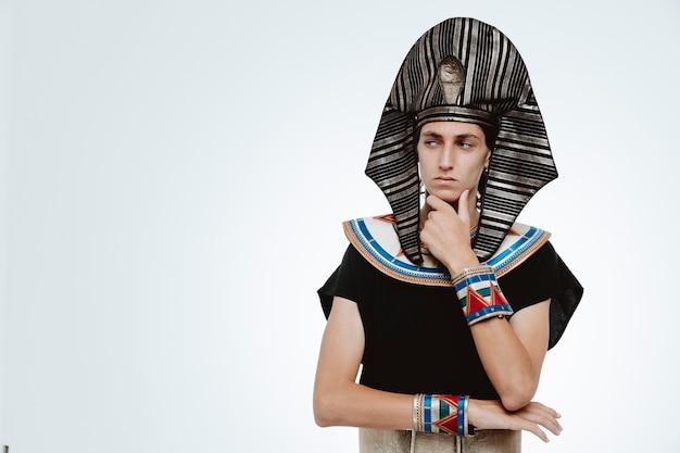 Mężczyzna w starożytnym egipskim stroju, patrzący na bok z zamyślonym wyrazem twarzy, myślący z ręką na brodzie na białym tle